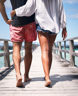 Buy stock photo Rearview shot of an unrecognizable couple walking arm in arm along the boardwalk together during a vacation in Indonesia