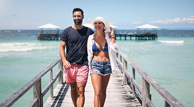 Buy stock photo Cropped shot of a happy young couple walking arm in arm down a boardwalk during a vacation together