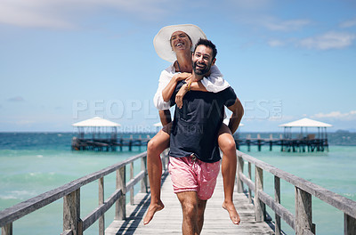 Buy stock photo Cropped shot of a handsome young man giving his girlfriend a piggy back ride along the boardwalk while on vacation
