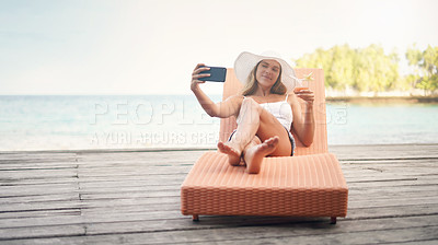 Buy stock photo Full length shot of an attractive young woman sitting on a sun lounger and taking selfies while holding a cocktail