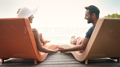 Buy stock photo Rearview shot of a happy young couple sitting on sun loungers together and holding hands while on vacation
