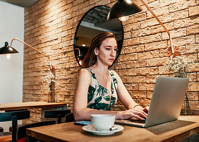 Buy stock photo Cropped shot of an attractive young businesswoman sitting in a coffee shop alone and working on her laptop