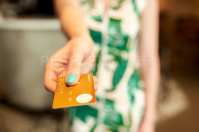 Buy stock photo Cropped shot of an unrecognizable woman standing alone in a coffee shop and holding out a credit card