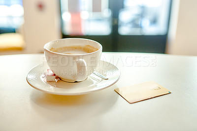 Buy stock photo Cropped shot of a freshly brewed cappuccino on the tabletop next to a credit card in an empty cafe