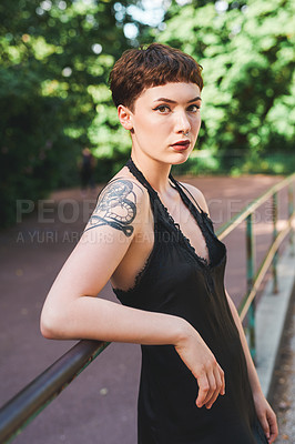 Buy stock photo Cropped portrait of an attractive young woman looking serious while leaning against a railing in a park during the day