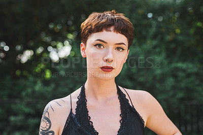 Buy stock photo Cropped portrait of an attractive young woman looking serious while standing in a park during the day