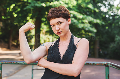 Buy stock photo Cropped portrait of an attractive young woman flexing her bicep while standing in a park during the day