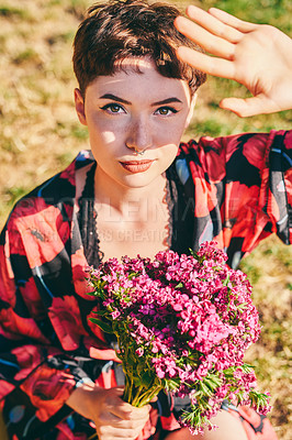 Buy stock photo Cropped portrait of an attractive young woman holding a bunch of flowers while sitting in a park during the day