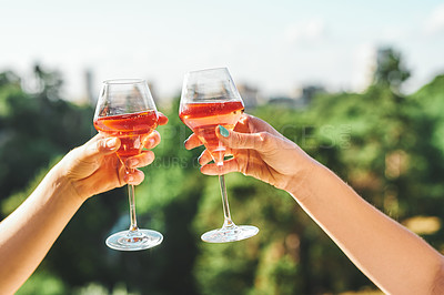 Buy stock photo Cropped shot of two unrecognizable girlfriends making a toast with wineglasses in a park during the day