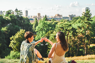 Buy stock photo Rearview shot of two affectionate young girlfriends making a toast with wineglasses while sitting in a park in a foreign city