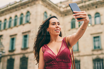 Buy stock photo Cropped portrait of an attractive young woman standing and taking a selfie with her cellphone during a tour of Barcelona