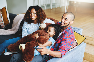 Buy stock photo Cropped shot of a happy young family of three watching tv together in their living room at home