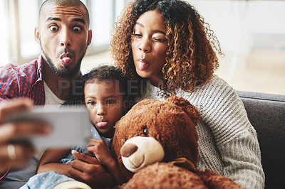 Buy stock photo Cropped shot of a happy young family of three posing for a selfie together in their living room at home