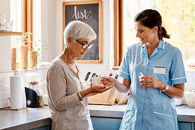 Buy stock photo Shot of a young nurse giving medication to a senior woman in a retirement home