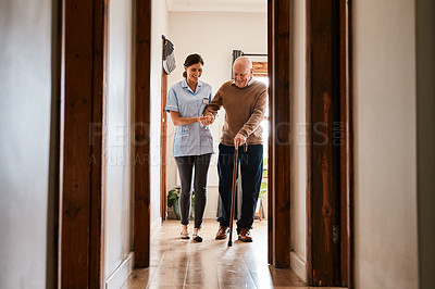 Buy stock photo Shot of a young nurse assisting a senior man with a walking stick in a retirement home