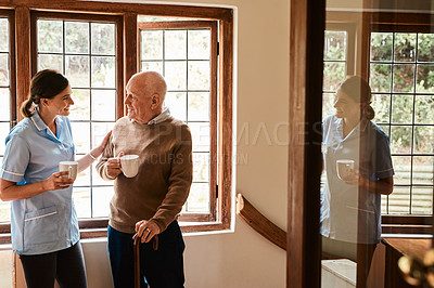 Buy stock photo Shot of a senior man and a young nurse having tea while chatting in a retirement home
