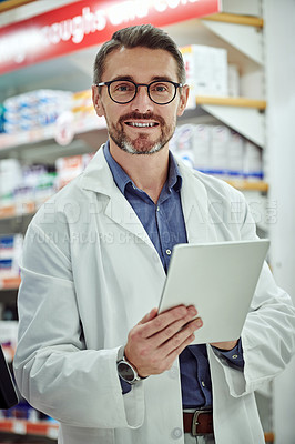 Buy stock photo Cropped shot of a pharmacist using a digital tablet while working in a chemist