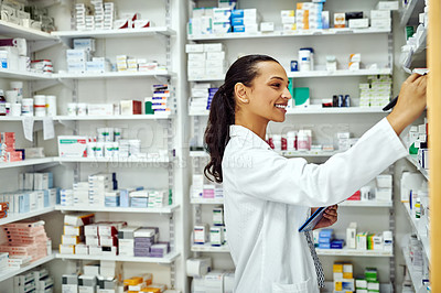 Buy stock photo Cropped shot of a female pharmacist reaching for medication on a shelf