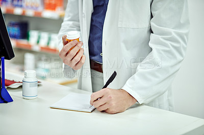 Buy stock photo Cropped shot of an unrecognizable pharmacist making notes while holding a product