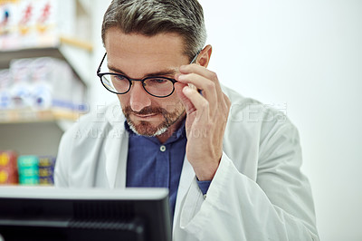 Buy stock photo Cropped shot of a male pharmacist using a computer at work