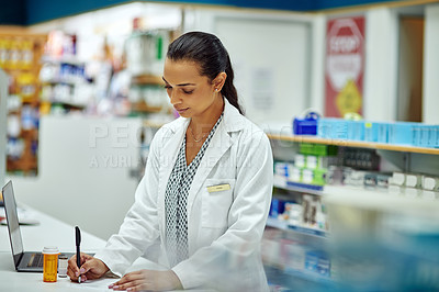 Buy stock photo Shot of a female pharmacist working in a chemist