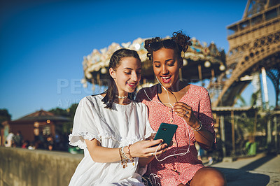 Buy stock photo Shot of two happy young women using a smartphone together at a carnival
