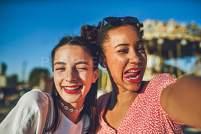 Buy stock photo Shot of two happy young women taking selfies together at a carnival