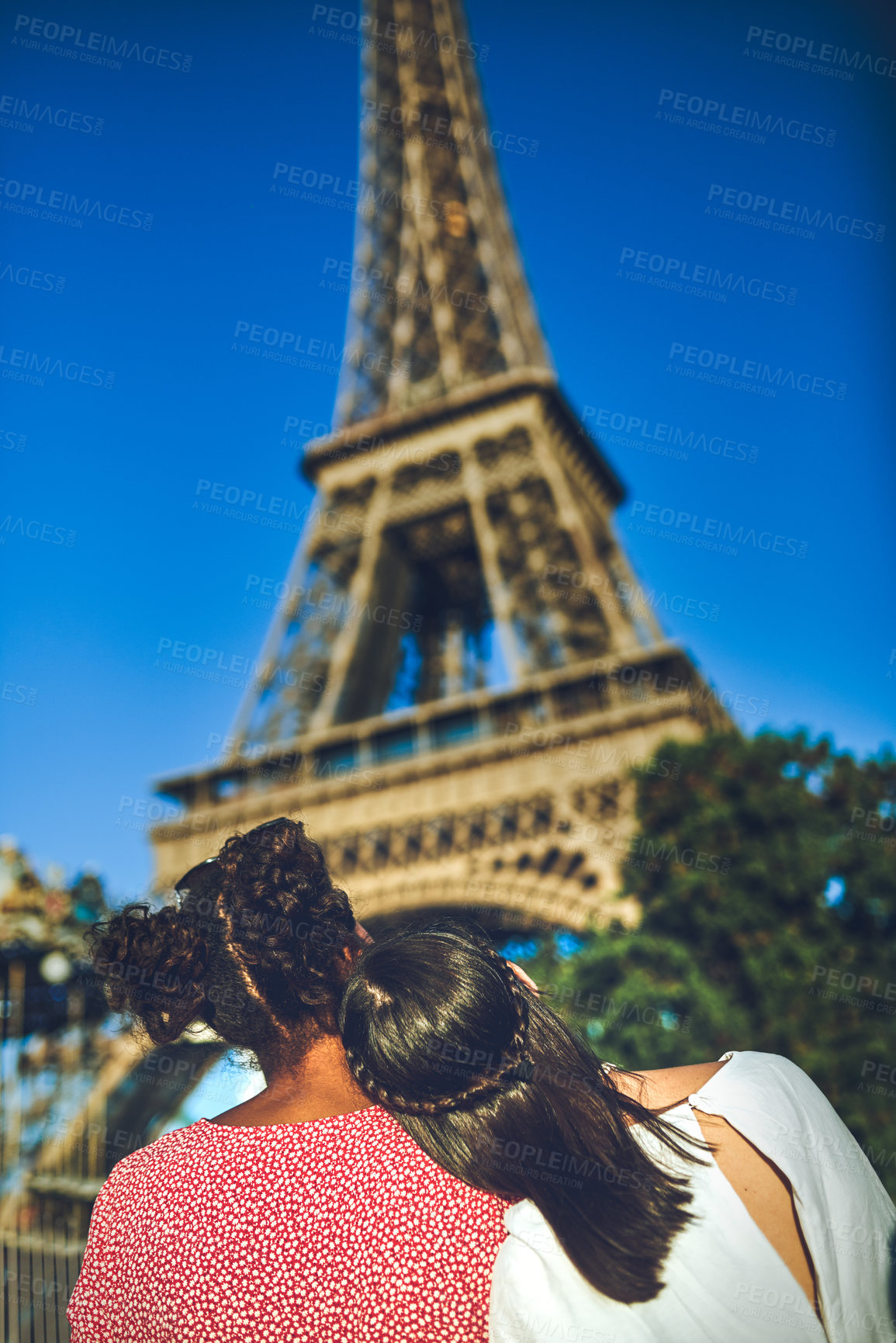 Buy stock photo Rearview shot of two young women admiring The Eiffel Tower at a carnival
