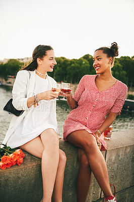 Buy stock photo Shot of two attractive young women sitting and drinking wine together alongside a canal in Paris, France
