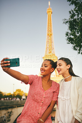 Buy stock photo Portrait of two attractive young women taking selfies together with a cellphone outdoors in Paris, France