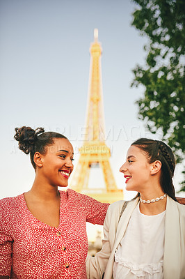 Buy stock photo Shot of two attractive young women relaxing together outdoors with the Eiffel Tower in the background in Paris, France