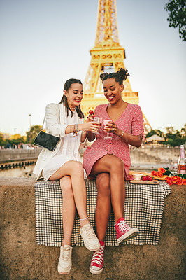 Buy stock photo Shot of two attractive young women having a picnic together outdoors in Paris with the Eiffel Tower in the background
