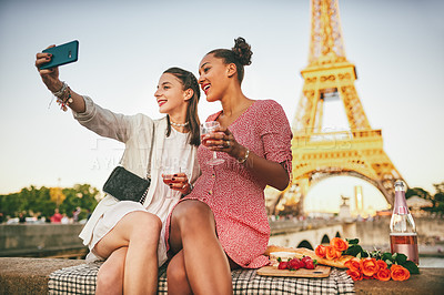 Buy stock photo Portrait of two attractive young women having a picnic and taking selfies together with a cellphone outdoors in Paris, France