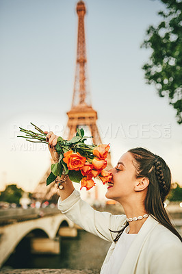 Buy stock photo Shot of an attractive young woman smelling a bouquet of lovely roses outdoors in Paris, France