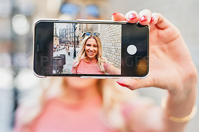 Buy stock photo Cropped portrait of an attractive young woman standing alone and holding up her cellphone for a selfie while on holiday