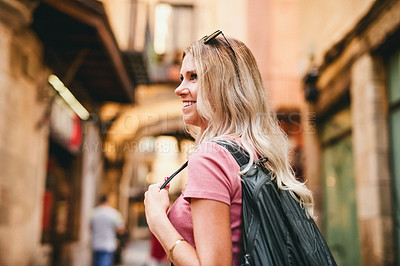 Buy stock photo Cropped shot of an attractive young woman wearing a backpack and standing alone while touring Barcelona