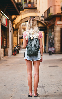 Buy stock photo Rearview shot of an attractive young woman wearing a backpack and standing alone while touring Barcelona