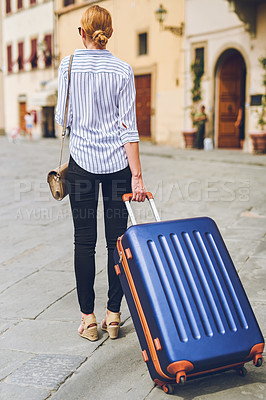 Buy stock photo Rearview shot of a woman walking with her luggage in a foreign city