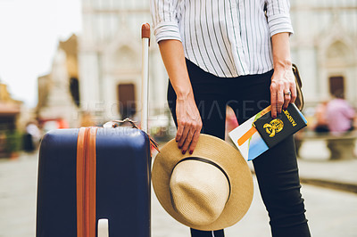 Buy stock photo Shot of an unrecognizable woman standing  next to her luggage bag while holding a hat and her passport