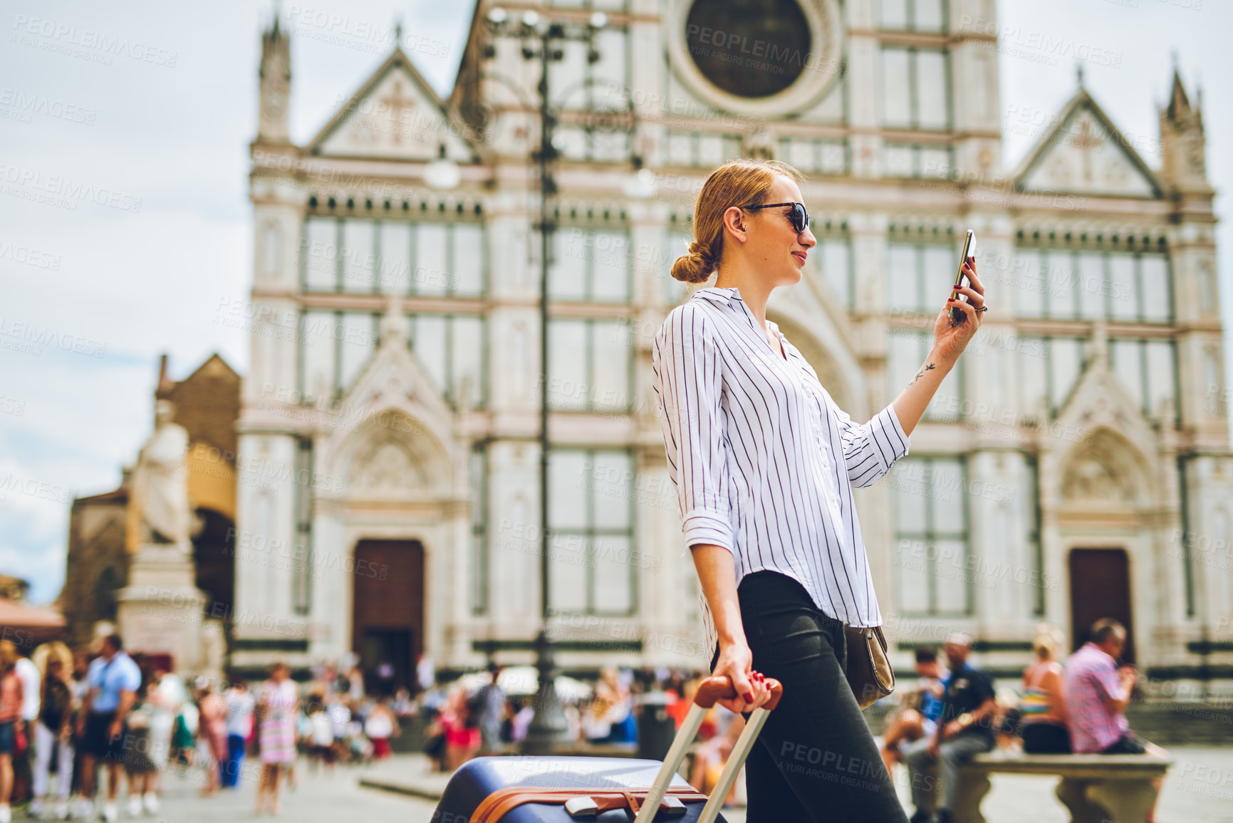 Buy stock photo Shot of a woman holding onto her luggage while using her cellphone in a foreign city