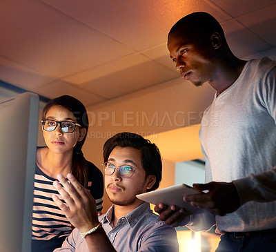 Buy stock photo Shot of colleagues looking at something on a computer while working late at the office