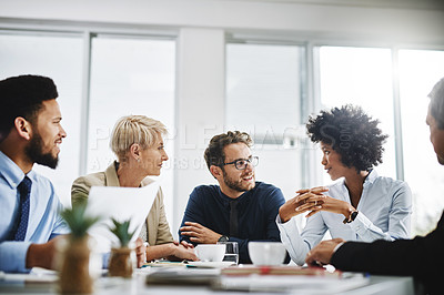 Buy stock photo Cropped shot of a diverse group of businesspeople sitting together and having a meeting in the office