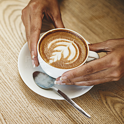 Buy stock photo Cropped shot of an unrecognizable woman sitting alone in a cafe and holding a cup of cappuccino