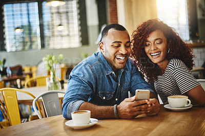Buy stock photo Cropped shot of a happy young couple sitting together and using a cellphone during a coffee date at a cafe