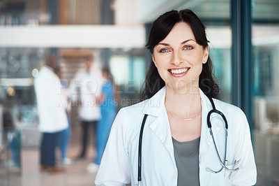 Buy stock photo Portrait of a confident doctor working in a hospital with her colleagues in the background