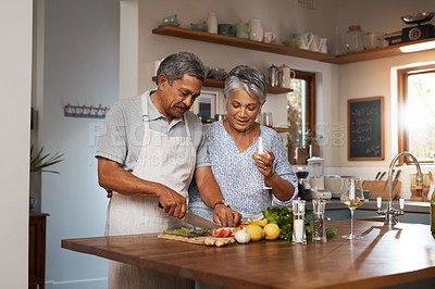 Buy stock photo Shot of a happy mature couple drinking wine while cooking a meal together at home