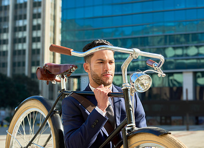Buy stock photo Shot of a handsome young businessman carrying and walking with his bicycle while traveling to work in the city