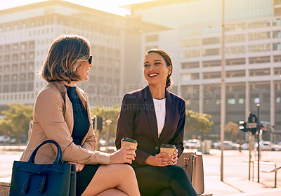 Buy stock photo Shot of two attractive young businesswomen having coffee and conversing together in the city