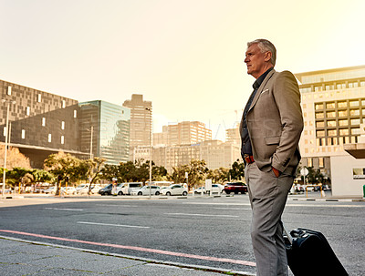 Buy stock photo Shot of a mature businessman walking with his suitcase in the city