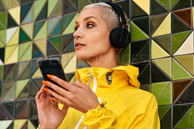 Buy stock photo Cropped shot of an attractive young woman standing against a wall and listening to music from her cellphone through headphones